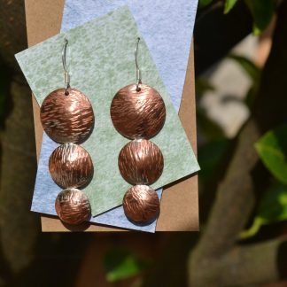 Textured drop copper earrings on .925 silver hookwires. Three individual discs soldered together, each one is slightly smaller than the one above, textured with an old hammer, the textured surface allows the light to bounce. The texture reminds me of grass blown by the wind. These are lightweight but large enough to make a statement. No two pair are the same.