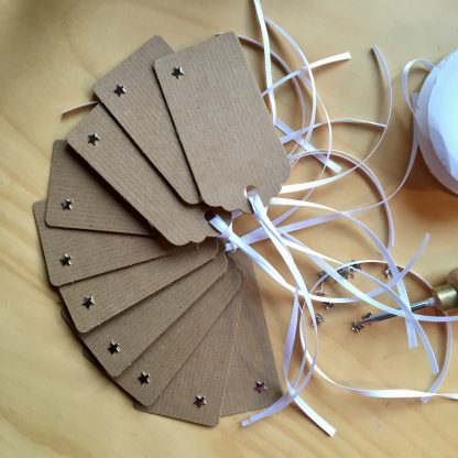 kraft gift tags with silver star pins and white ribbon