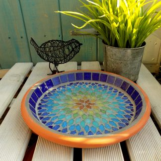 Mosaic birdbath with a bohemian mandala style design radiating rainbow colours.