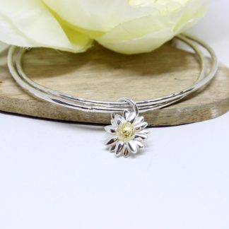 Silver stacking bangles and daisy charm