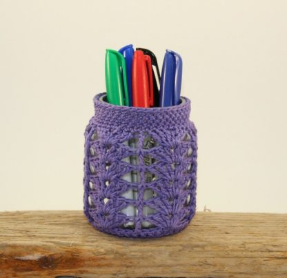 A crochet covered jar used as a pen pot