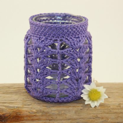 a jam jar covered in purple crochet in a lacey pattern