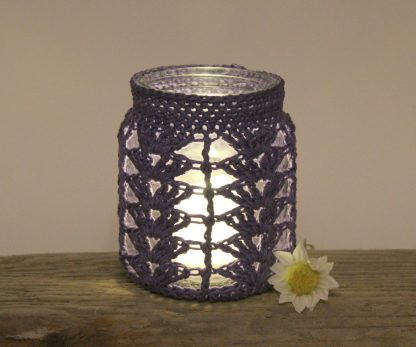 A jam jar covered in crochet with a lit tealight inside