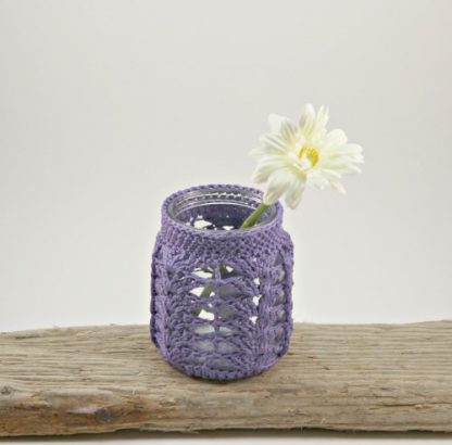 A purple crochet covered jar used as a vase