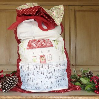 Shows a red Christmas Stocking/Santa sack with traditional Christmas cottage