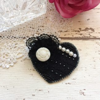 Handmade bead embroidered heart shaped brooch featuring vintage black lace, buttons and pearls.