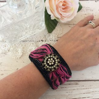Handmade bead embroidered cuff featuring shibori ribbon and a vintage focal piece.