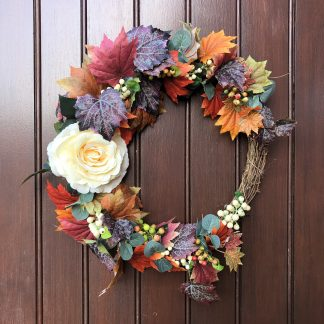 Autumn leaves and a cream rose on a front door wreath