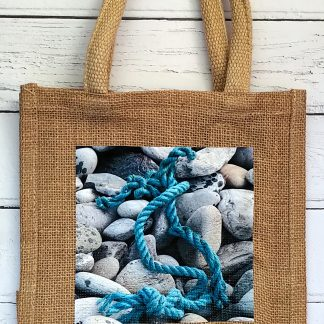 small jute bag with rope and pebbles photo