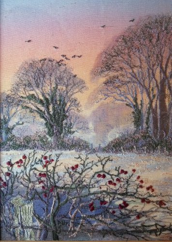 A machine embroidered Thread Painting of Hawtrhorn berries in a hedge looking across a field to winter trees with late evening glow in the sky around November and feels misty and coldter tree