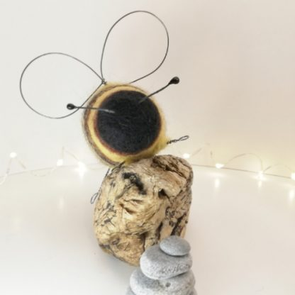 Bee sculpture on top of driftwood