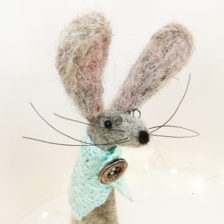 needle felted wool sculpture of a hare lookung like an old lady wearing a buttoned cape and spectacles