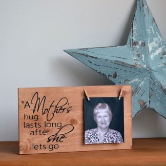 Natural wood sign with a photo on the right held by pegs and writing to the left saying A Mother's hug lasts long after she lets go, sat on a wood shelf in front of a blue star