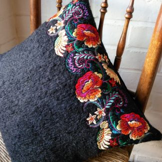 Chair displayed with black cushion with red floral embroidery down one edge