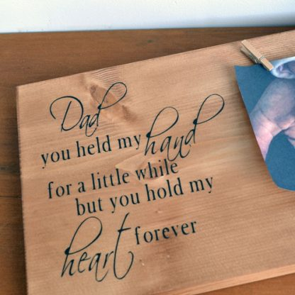 Wooden rectangle sign laying on a wooden shelf with two pegs holding a photo and the words Dad you held my hand for a little while but you hold my heart forever