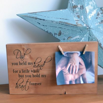 Wooden rectangle stood next to a star and on a shelf with two pegs holding a photo and the words Dad you held my hand for a little while but you hold my heart forever