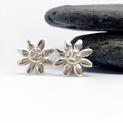 silver daisy cufflinks in front of grey slate stones on a white background