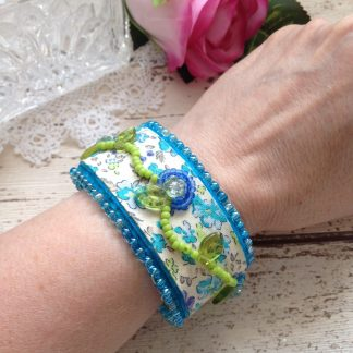 Handmade bead embroidered textile cuff featring ditsy floral fabric.
