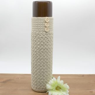 a brown narrow vase covered in ecru crochet decorated with three wooden buttons