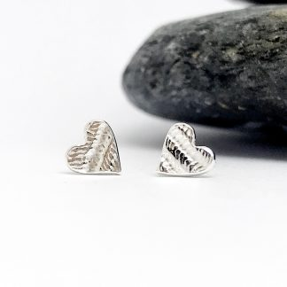 textured heart earrings next to a grey slate stone on a white background