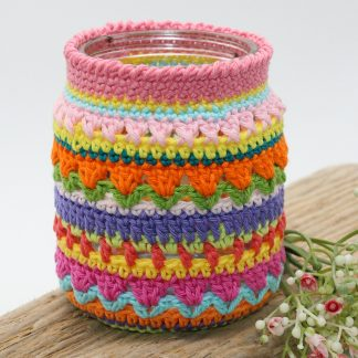 A jam jar covered in multi coloured crochet