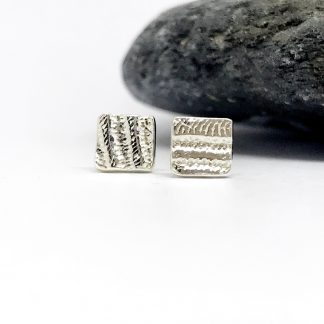 Tiny square stud earrings with an abstract texture next to grey slate stone on a white background