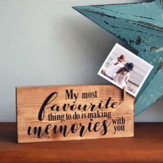 A wooden block with text 'My most favourite thing to do is making memories with you' to the front. The block has a peg holding a photograph to the side and is stood on a wooden shelf in front of a large blue star.