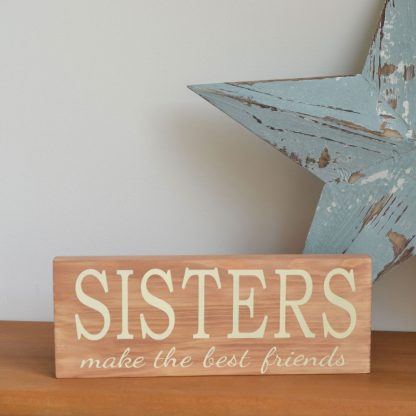 Wooden block stood on a wood shelf with the words 'Sisters Make The Best Friends' to the front in cream text with a large blue star stood behind it.