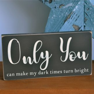 A brown wooden sign stood on a wooden shelf in front of a blue star. The front of the sign in cream text are the words 'Only You can make my dark times turn bright'