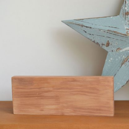 Wooden block stood on a wood shelf with a large blue star stood behind it.