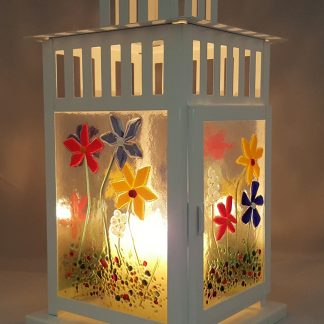 glass panelled candle lantern with summer flower decorative pattern on the glass and lit candle inside