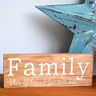 Natural wooden block with white text to the front that reads 'Family where life begins and love never ends'. The block is stood on a wooden shelf in front of a large blue star.