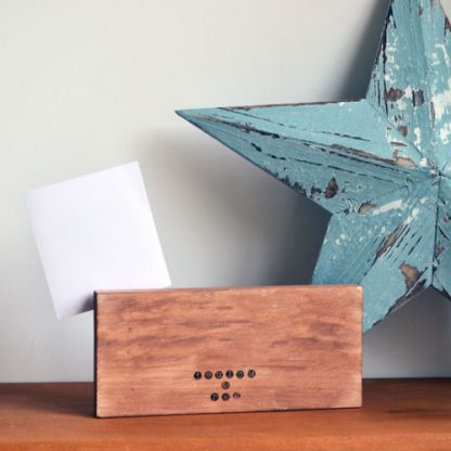 A wooden block that has a peg holding a photograph to the side and is stood on a wooden shelf in front of a large blue star.