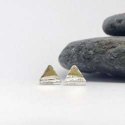 silver triangle earrings topped with gold like little mountains sitting in front of a grey slate stone of=na white background