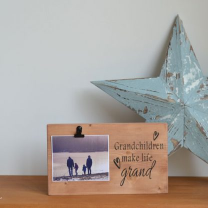 Wooden rectangle photo holder with the words Grandchildren make life grand to the front with a clip holding a photo, standing on a wooden shelf in front of a blue star
