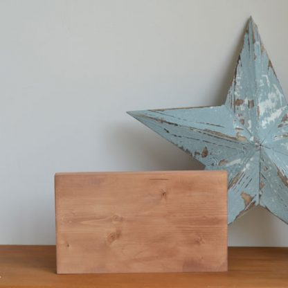 Wooden rectangle photo holder, standing on a wooden shelf in front of a blue star