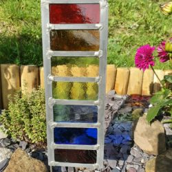 Stained Glass Rainbow garden stake planted in border