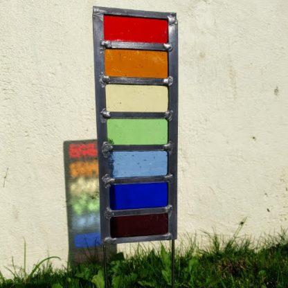 Stained Glass Rainbow garden stake planted against wall