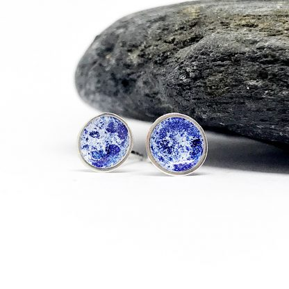 blue enamel and silver earrings in front of a grey stone on a white background