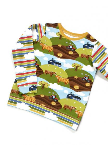 Farm print childrens top with highland cows and clouds.