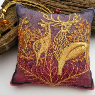 Rich autumn colours are embroidered with a golden stag and two hinds on this embroidered and scented lavender pouch with beaded hanging loop