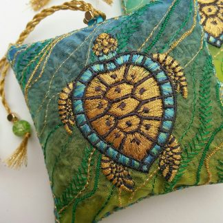 Ocean TURTLE swimming against seaweed sweeping across the current, in green and blue water with rich gold embroidery for this lavender bag design, by Pauline Thomas