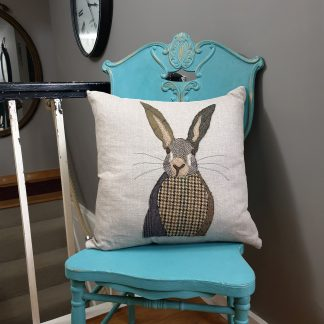 Hare appliqued linen cushion sitting on a chair