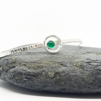 Green Onyx a textured Sterling Silver Bangle balanced on a grey slate stone with a white background