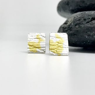 texture silver earrings with an abstract pattern of gold applied by keum boo sit-in in front of grey slate stones on a whit background