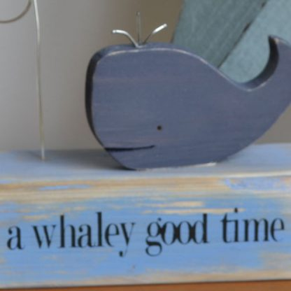 A wood blue whale diorama photo holder sat on a shelf in front of a blue star