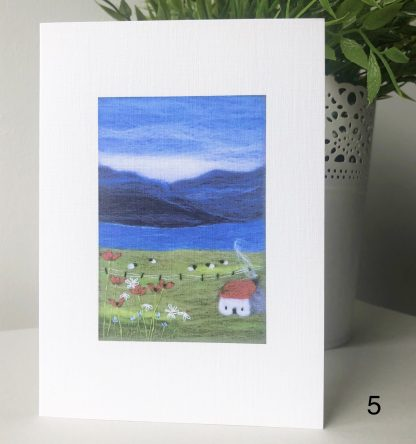 A6 printed card of Scottish Wool Art landscape hills and loch with red roofed cottage sheep and flowers