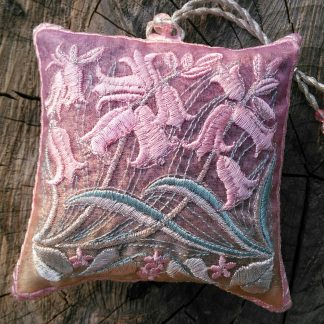 A pastel pink coloured lavender bag with pink coloured Bluebell flowers embroidered design postitioned on a weathered log