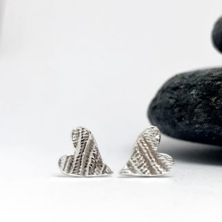 Silver asymmetrical heart earrings next to grey slate stone on a white background