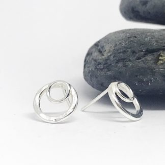hammered silver double circle double studs earrings sitting next to grey slate stones on a white background